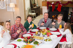 Smiling family toasting to camera during christmas dinner Royalty Free Stock Photography