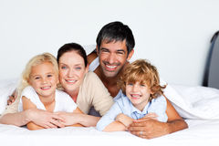 Smiling family together on bed. Smiling family lying together on bed Royalty Free Stock Photography