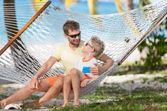 Family on vacation. Smiling family of two, father and son, enjoying summer tropical vacation together in hammock, father`s day concept Stock Images