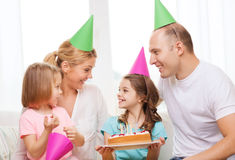 Smiling family with two kids in hats with cake Royalty Free Stock Photo