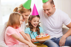 Smiling family with two kids in hats with cake Stock Images