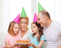Smiling family with two kids in hats with cake Stock Photo