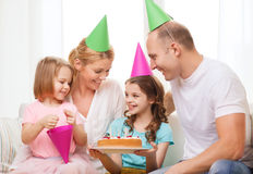 Smiling family with two kids in hats with cake Royalty Free Stock Photos