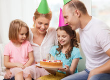 Smiling family with two kids in hats with cake Stock Photography
