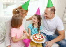 Smiling family with two kids in hats with cake Stock Image