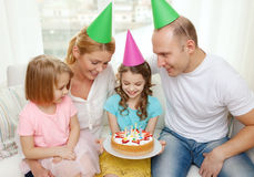 Smiling family with two kids in hats with cake Royalty Free Stock Images