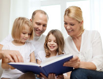 Smiling family and two little girls with book Royalty Free Stock Images