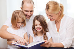 Smiling family and two little girls with book Stock Images