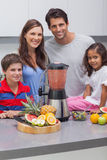 Smiling family using a blender together Stock Photo