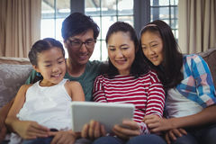 Smiling family using digital tablet together in living room Stock Images