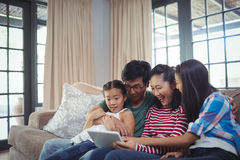 Smiling family using digital tablet together in living room Royalty Free Stock Photos