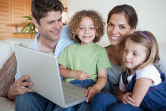 Smiling family using a laptop. In their living room Stock Images
