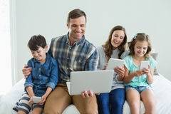 Smiling family using laptop, digital tablet and mobile phone in bedroom Stock Photo