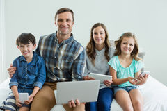 Smiling family using laptop, digital tablet and mobile phone in bedroom Royalty Free Stock Photography