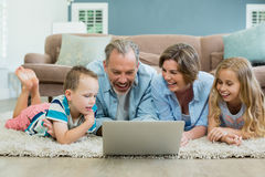 Smiling family using laptop while lying on carpet in living room. At home Royalty Free Stock Photography