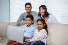 Smiling family using laptop on sofa. Smiling family using laptop on the sofa in living room Royalty Free Stock Images