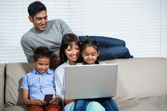 Smiling family using laptop on the sofa. In living room Stock Photography