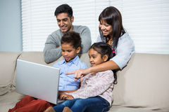 Smiling family using laptop on the sofa Royalty Free Stock Photography