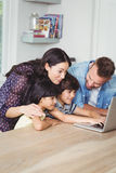 Smiling family using laptop together Stock Image