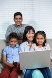 Smiling family using technology on the sofa. Smiling family using laptop and smartphone on the sofa in living room Royalty Free Stock Image