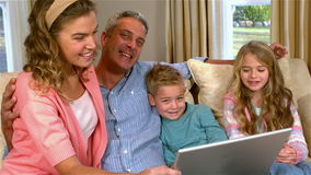 Smiling family using technology. On sofa in slow motion stock video footage