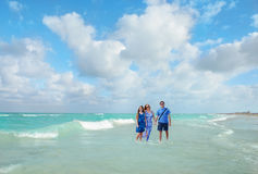 Smiling family walking on beautiful beach. Royalty Free Stock Photography