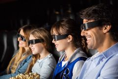 Smiling Family Watching 3D Movie In Theater Stock Image