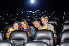 Smiling Family Watching Film In Theater Stock Photo