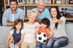 Smiling family watching football match Stock Photo