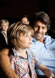 Smiling Family Watching Movie In Theater. Happy father looking at son watching movie in cinema theater Stock Photo