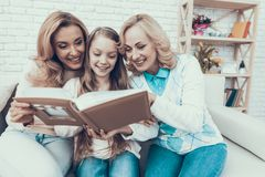Smiling Family Watching into Photo Album on Sofa royalty free stock photography
