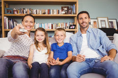 Smiling family watching television. While sitting on sofa at house Royalty Free Stock Image
