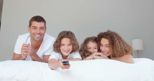 Smiling family watching TV. In bedroom stock video