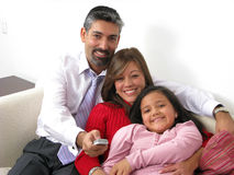 Smiling family watching TV in the living room stock photography