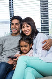 Smiling family watching tv on the sofa. In living room Stock Image