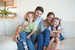 Smiling family watching TV together Stock Images