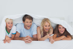Smiling family watching TV. Under the blanket Stock Photos