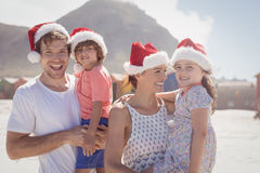 Smiling family wearing Santa hat. During sunny day at beach Royalty Free Stock Photography