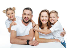 Smiling family in white t-shirts hugging. On white background royalty free stock photos