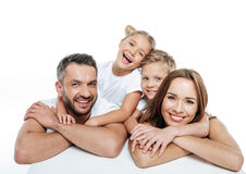 Smiling family in white t-shirts hugging. On white background Royalty Free Stock Photography