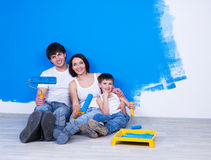 Smiling Family With Paintbrush Near The Wall Stock Photo