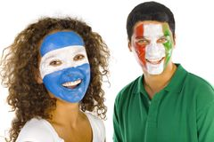 Smiling fans. Portrait of young, Argentinian and  Italian sport's fans with painted flags on faces. Smiling and looking at camera.  Front view, white background Stock Photo