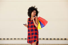 Smiling farina american woman with bags and cellphone Stock Images