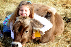 Smiling farm girl and pet calf. A smiling pretty young farm girl with long blond hair, loving her pet calf. Shallow depth of field Stock Photography