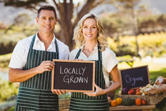 Smiling farmer couple holding locally grown sign. Portrait of a farmer couple holding locally grown sign stock image