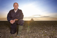 Smiling farmer cupping wheat seed in ploughed field with tractor in background Royalty Free Stock Images