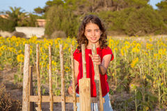 Smiling farmer girl with sunflowers field holding fence door Royalty Free Stock Image