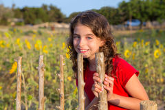 Smiling farmer girl with sunflowers field holding fence door Royalty Free Stock Photos