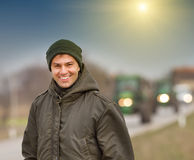 Smiling farmer. Happy farmer standing on farmland with tractors in background stock photos