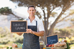 Smiling farmer holding a locally grown sign Stock Images